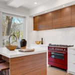 duo tone white and cherry stain wood kitchen with island and waterfall island quartz backsplash